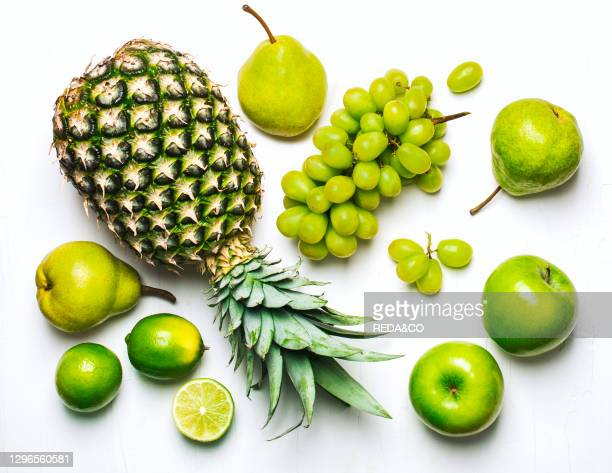 Green fruits on a white background. Fresh organic produce. Healthy food. Top view.