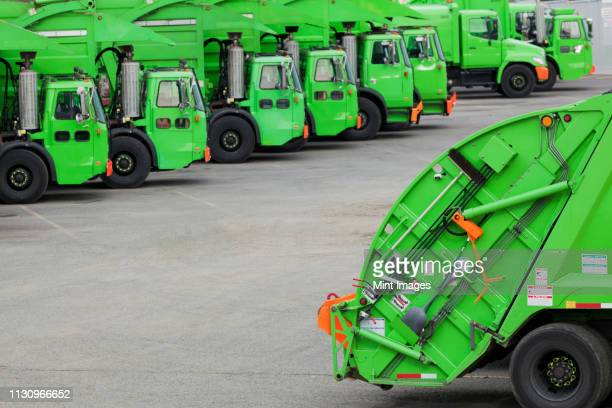 green garbage trucks in parking lot - garbage truck stock pictures, royalty-free photos & images