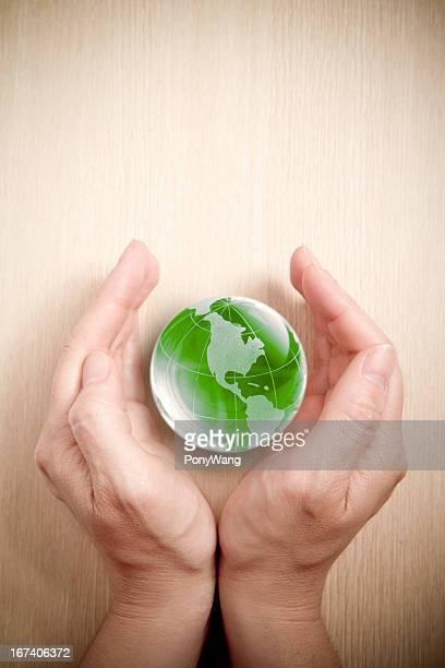 グリーンのガラスグローブを手