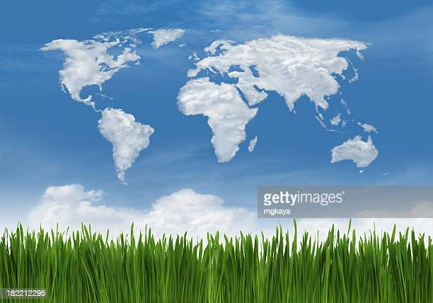 Green grass against sky with world outline in clouds
