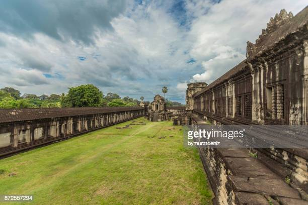 green grass outside of angkor wat temple in cambodia - khmer art stock photos and pictures