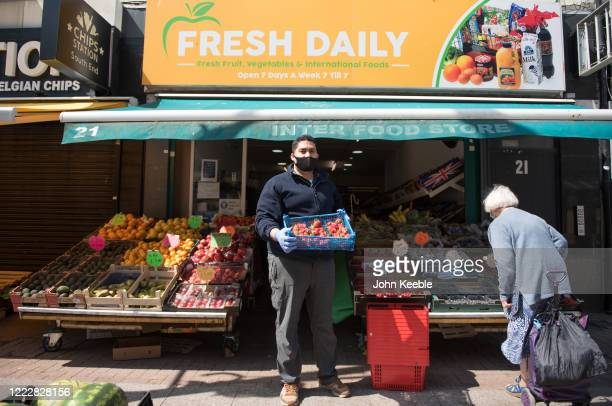 Green Grocer, Hammed wearing a face mask poses as he organises his fresh fruit, vegetable and international food shop which is one of only a very few...