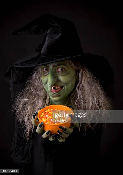 Green Halloween witch holding orange bowl of candy corn