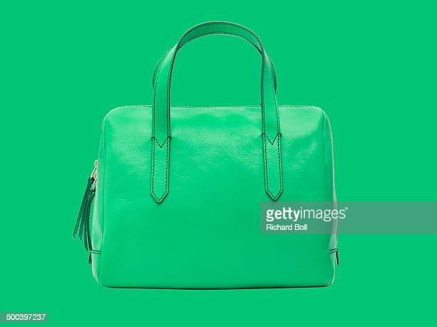 Green handbag against a green background