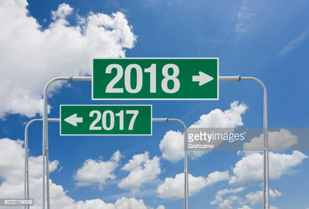 Green highway sign with exit for new year 2018