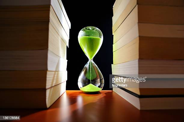 Green hourglass between stack of books