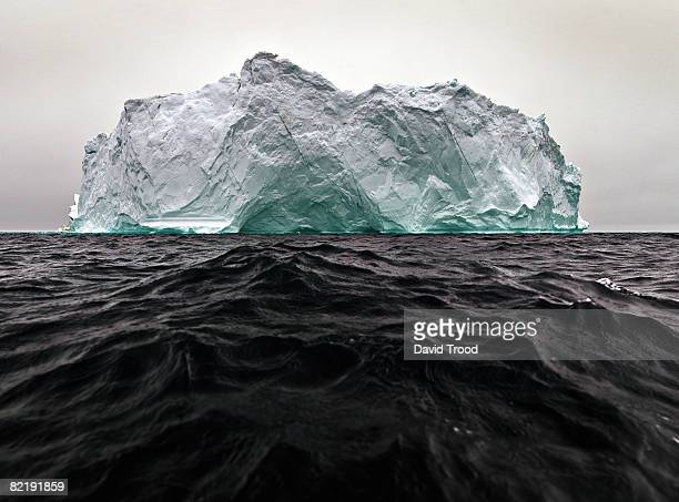 green iceberg floating in sea. - iceberg photos et images de collection