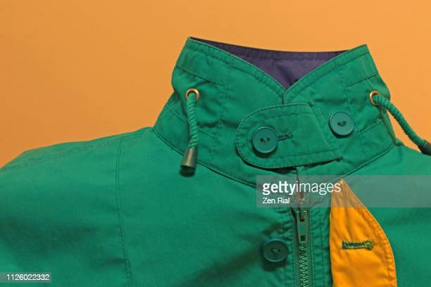 green jacket against yellow background showing buttoned up collar, zipper and lining - green jacket fashion item stock photos and pictures
