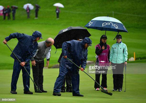 Green keepers squeege the 18th green as Brittany Altomare of USA waits to putt during the play off after the final round of The Evian Championship at...