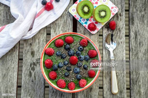Green kiwi smoothie with blueberries and raspberries and chia seeds in bowl