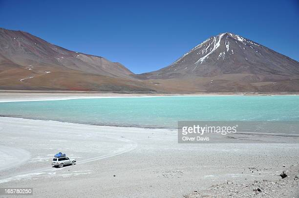 CONTENT] Green 'Laguna Verde' salt lake and snowspeckled Licancabur volcano landscape view with a 4x4 car in the foreground Popular destination on...