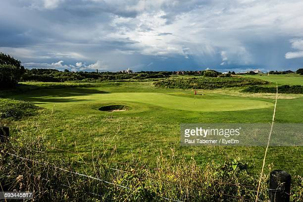 Green Landscape At Golf Course Against Cloudy Sky