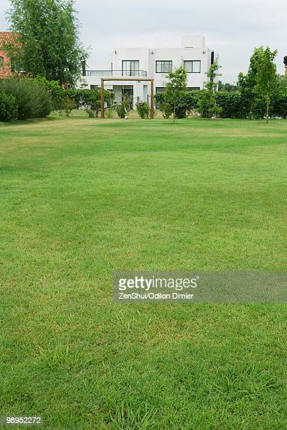 green lawn, swing set and home in distance - pelouse photos et images de collection