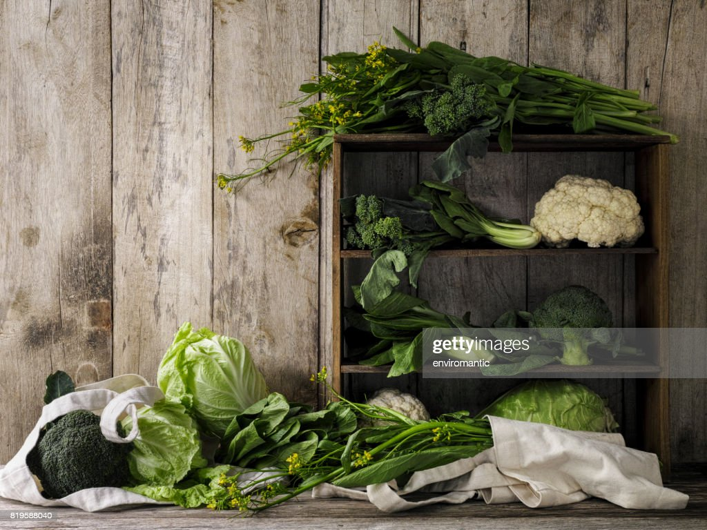 Green leafy vegetables on old rustic wooden shelves and an old weathered table against an old weathered wood plank wall background. : Stock Photo