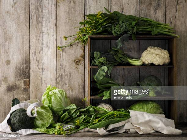 Green leafy vegetables on old rustic wooden shelves and an old weathered table against an old weathered wood plank wall background.