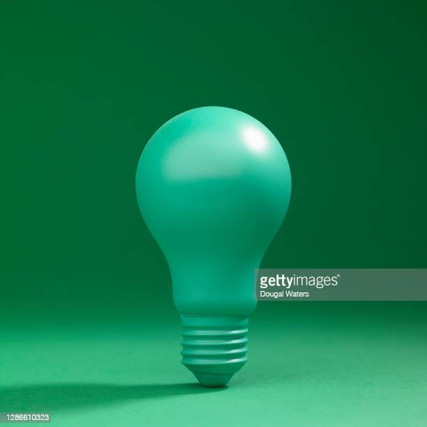 green light bulb on green background. - ideas stock pictures, royalty-free photos & images