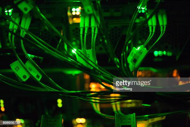 Green light illuminates optical cables connected to data rack servers in the server room of the Sberbank PJSC data processing center at the Skolkovo...