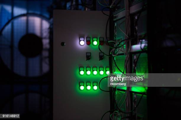 Green light illuminates the cases of mining rigs operating inside a shipping container converted into a mobile cryptocurrency mining farm operated by...