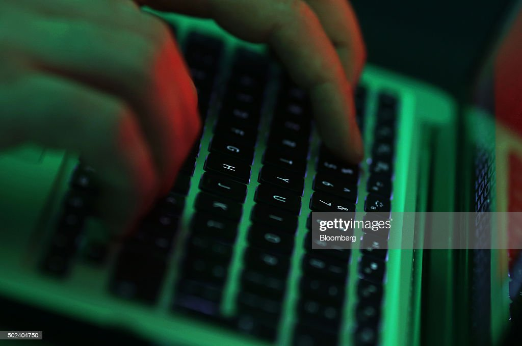 Green light illuminates the keyboard of laptop computer as a man enters the data using the computer keyboard in this arranged photograph in London, U.K., on Wednesday, Dec. 23, 2015. The U.K.s biggest banks fear cyber attacks more than regulation, faltering economic growth and other potential risks, and are concerned that a hack could be so catastrophic that it could lead to a state rescue, according to a survey. Photographer: Chris Ratcliffe/Bloomberg via Getty Images