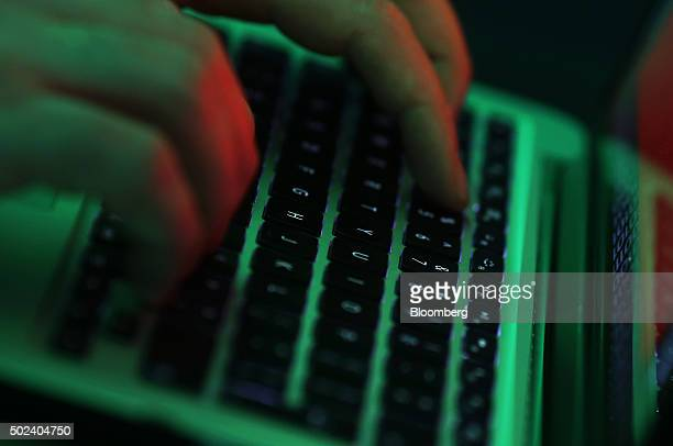 Green light illuminates the keyboard of laptop computer as a man enters the data using the computer keyboard in this arranged photograph in London UK...