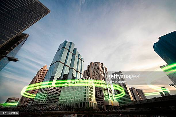 green light trails surrounding skyscrapers - surrounding stock pictures, royalty-free photos & images