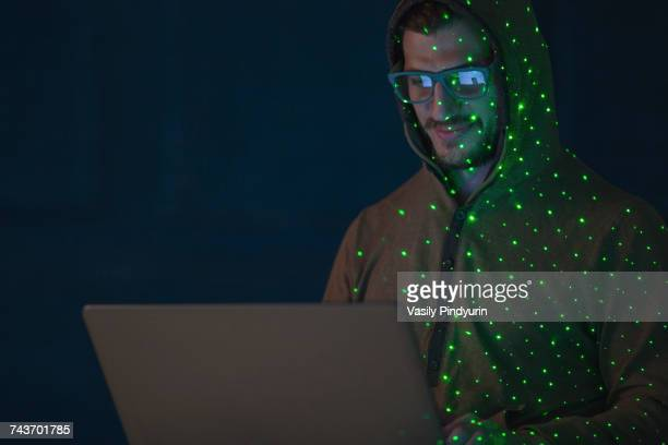 green lights over smiling computer hacker wearing hooded shirt using laptop - con man stock photos and pictures