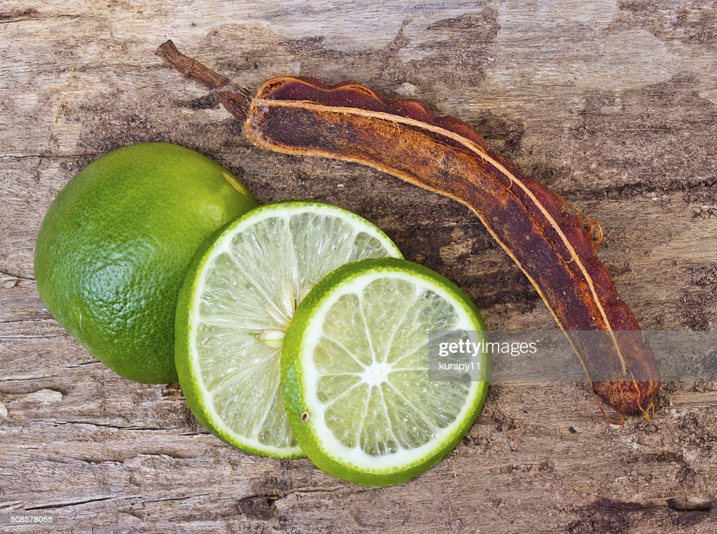 Green limes and tamarind on wooden background. : Stockfoto