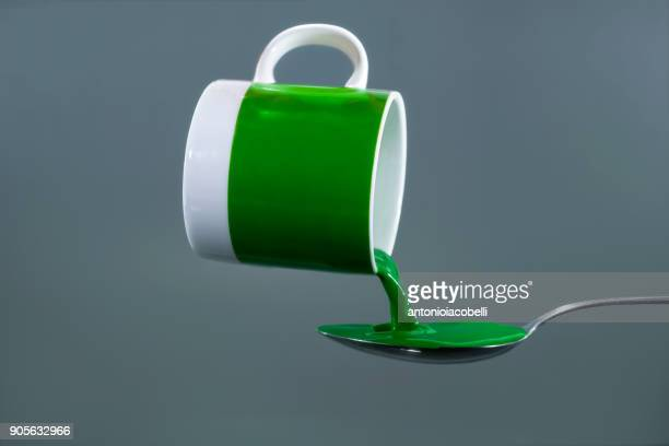 Green liquid in a mug being poured onto a spoon