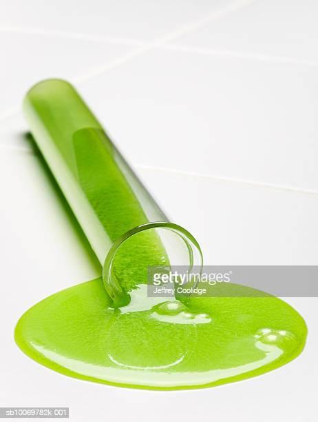 Green liquid spilling from test tube, studio shot