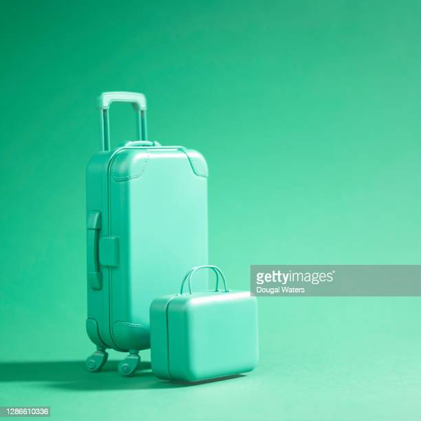 green luggage suitcase on green background. - suitcase stock pictures, royalty-free photos & images