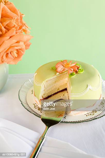 green marzipan cake with missing slice on table with roses - marzipan - fotografias e filmes do acervo