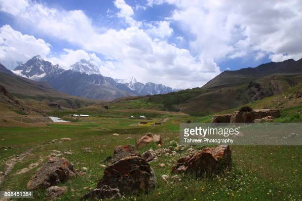 green meadows with snowy mountains in background - khyber pass stock pictures, royalty-free photos & images