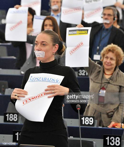 A Green member of Parliament wearing a gag over her mouth holds a blank page with the word 'censored' written on it as she demonstrates along fellow...