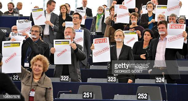 Green members of Parliament wearing gags over their mouths demonstrate against the Hungarian media law during Hungarian Prime Minister Viktor Orban's...