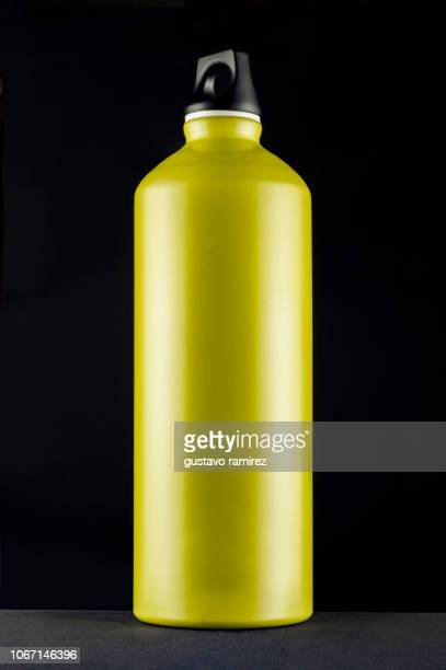 green metal bottle canteen on black background - canteen stock pictures, royalty-free photos & images
