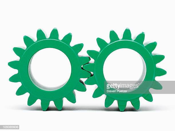 green metal gears interlocked - things that go together stock photos and pictures