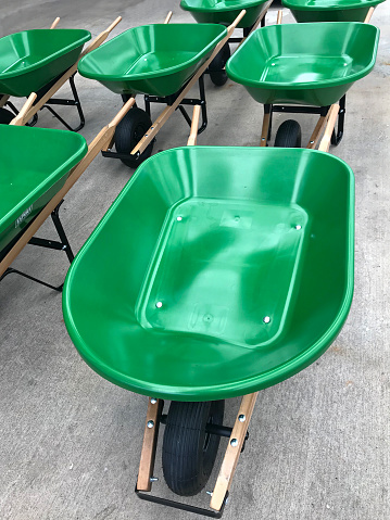 Green metal wheelbarrows on display for sale in a home improvement store - gettyimageskorea
