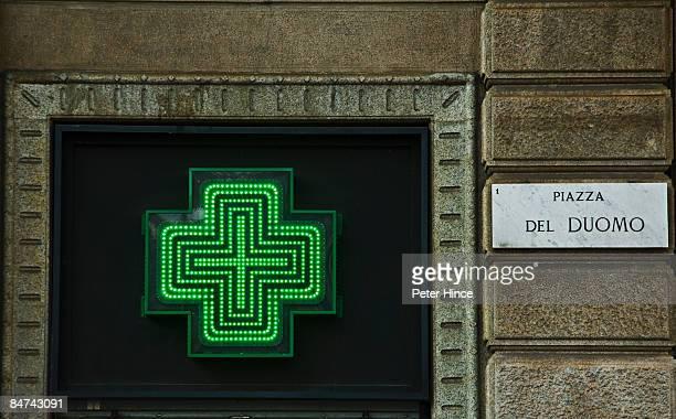 Green Neon cross of Farmacia next to street sign