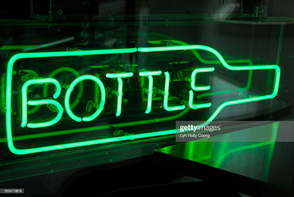 Green neon sign shaped as bottle in window of bar. : Stock Photo