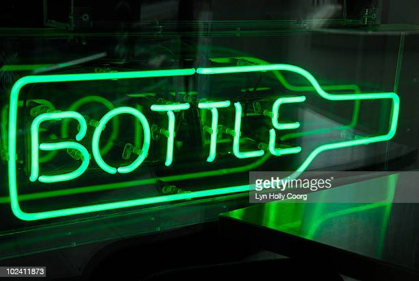 green neon sign shaped as bottle in window of bar. - lyn holly coorg stock pictures, royalty-free photos & images