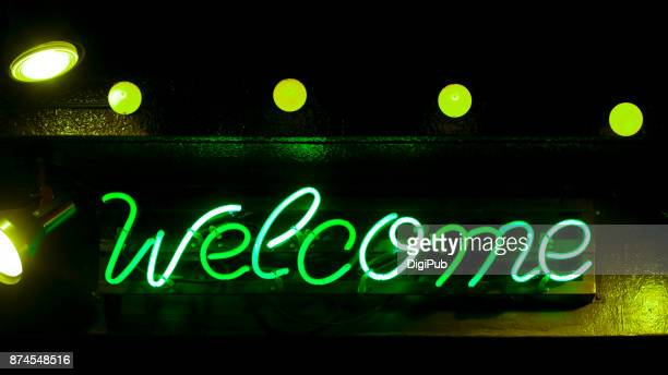 green neon sign - welcome - neon letters stock photos and pictures