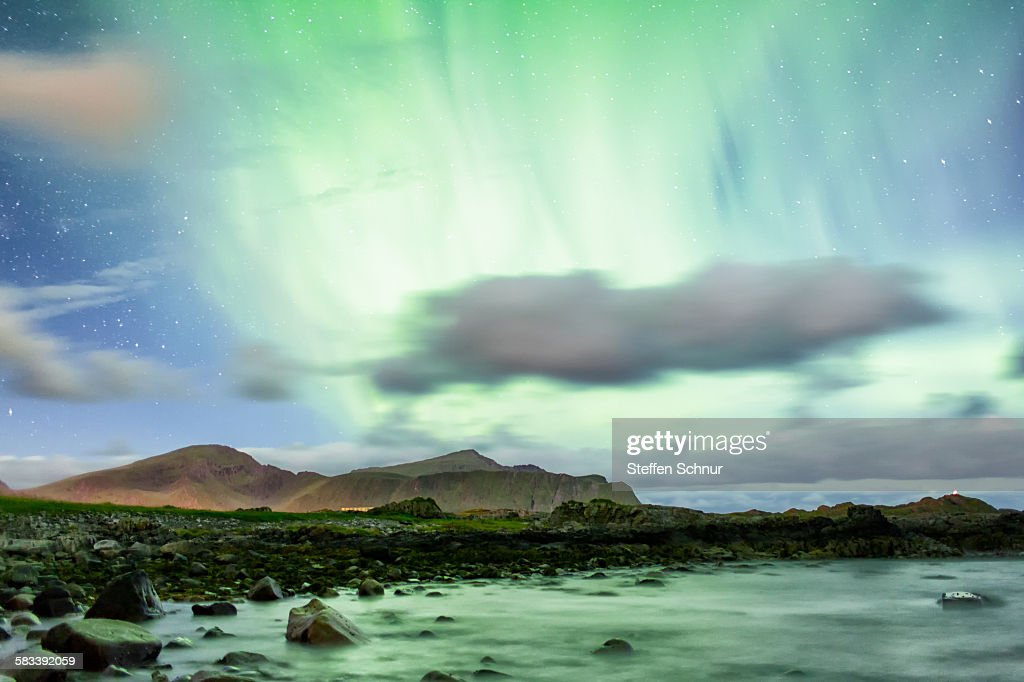 Green northern lights over the rocky coast Norway : Stock Photo