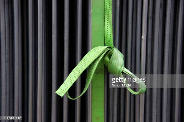 green nylon strap tying together steel railing barricade fencing - strap stock pictures, royalty-free photos & images