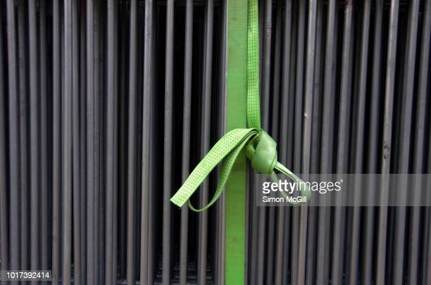 green nylon strap tying together steel railing barricade fencing - barricade stock pictures, royalty-free photos & images