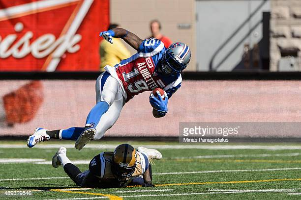 J Green of the Montreal Alouettes jumps over Demond Washington of the Winnipeg Blue Bombers during the CFL game at Percival Molson Stadium on...