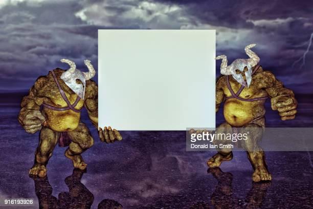 Green ogres holding blank sign