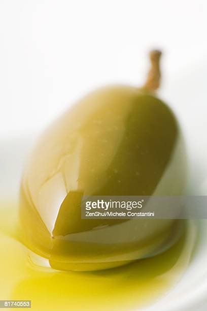 Green olive in olive oil, close-up