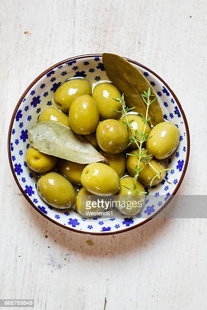 green olives in bowl with thyme and bay leaf - aceitunas fotografías e imágenes de stock