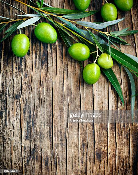 green olives on a wooden table - green olive ストックフォトと画像