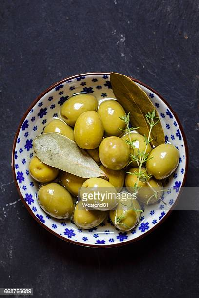 green olives thyme and bay leaves in bowl - green olive stock photos and pictures